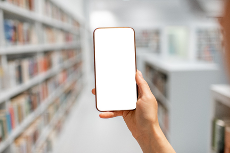 Mockup image of smartphone with modern library interior on the background