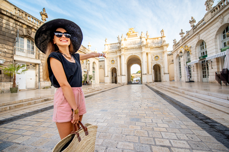 Portrait of a young woman tourist standing in front of the triumphal arch traveling in Nancy city