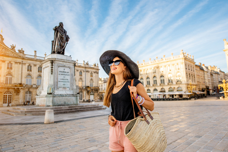 Young woman tourist enjoying beautiful morning view on the central square traveling in Nancy city in France