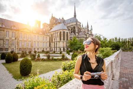 Young woman enjoying beautiful view on the Reims cathedral and gardens traveling in Reims city, France. Woman is out of focus