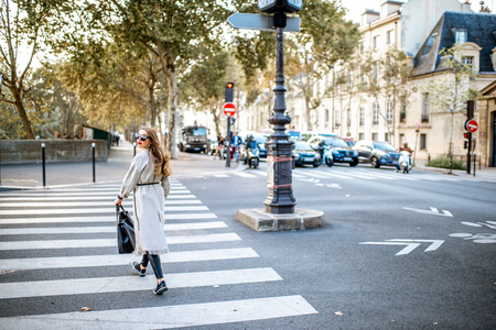 Cityscape view with woman crossing the street during the morning light in Paris, France