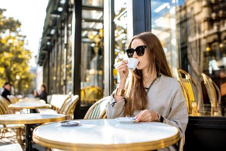Portrait d'une jeune femme appréciant le café assis à l'extérieur au café français traditionnel pendant la matinée à Paris