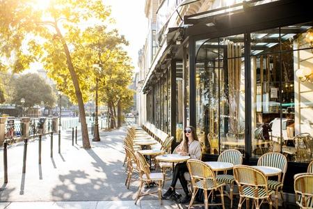 Vue sur la rue sur le café traditionnel français avec jeune femme assise à l'extérieur pendant la lumière du matin à Paris