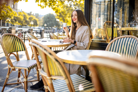 Portrait of a young woman enjoying coffee sitting outdoors at the traditional french cafe during the morning in Paris Foto de archivo - 109823746
