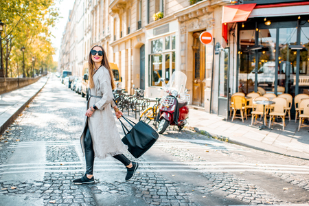 Street view with traditional french cafe and woman walking during the morning in Paris Imagens
