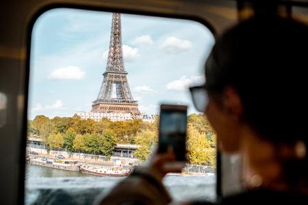 Jeune femme photographiant avec smartphone tour Eiffel de la rame de métro à Paris. Image centrée sur la tour
