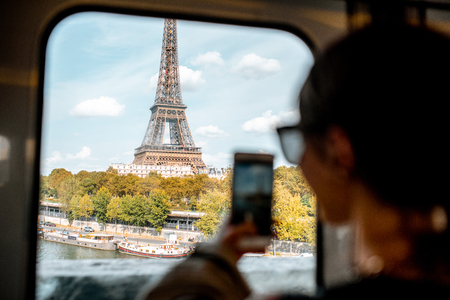 Young woman photographing with smartphone Eiffel tower from the subway train in Paris. Image focused on the tower Imagens