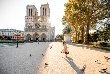 Morning view on the famous Notre-Dame cathedral with woman running on the square dispersing pigeons in Paris, France Stock Photo