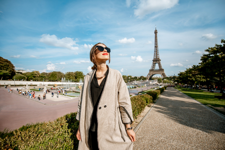 Lifestyle portrait of a young woman walking in front of the famous Eiffel tower during the sunny day in Paris Stock fotó