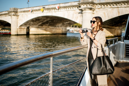 Young woman enjoying beautiful landscape view on the riverside from the tourist ship during the sunset in Paris