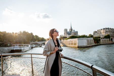 Young woman tourist enjoying beautiful landscape view on the riverside with Notre-Dame cathedral from the boat during the sunset in Paris