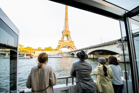 People enjoying beautiful landscape view on the riverside with Eiffel tower from the boat during the sunset in Paris