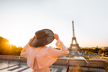 Woman enjoying great view on the Eiffel tower standing back with hat on the square early in the morning in Paris Stock Photo