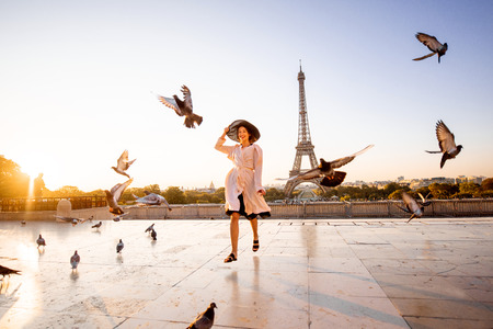 Woman running on the famous square dispersing pigeons with great view on the Eiffel tower early in the morning in Paris Stock Photo