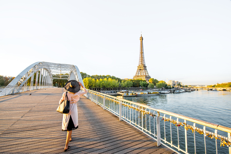 Landscape view on the river and Eiffel tower with woman walking on the footbridge during the morning light in Paris Banque d'images