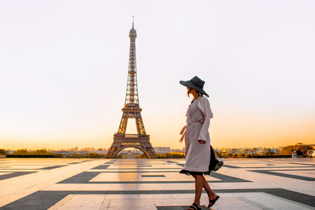 Woman dressed in coat and hat walking on the famous square with great view on the Eiffel tower early in the morning in Paris Stock Photo