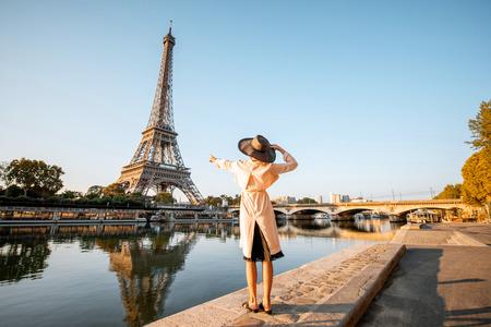 Jeune femme touristique bénéficiant d'une vue paysage sur la tour Eiffel avec beau reflet sur l'eau pendant la lumière du matin à Paris