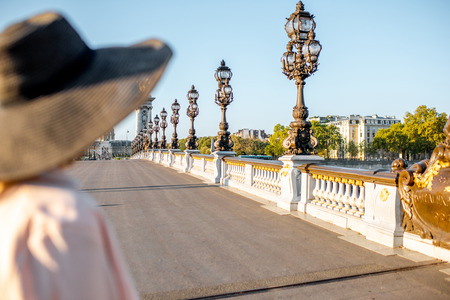 Woman looking on the famous Alexandre bridge with beautiful lanterns in Paris Stock Photo