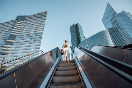 Stylish businesswoman in white suit going down on the escalator at the business centre outdoors with skyscrapers on the background in Paris