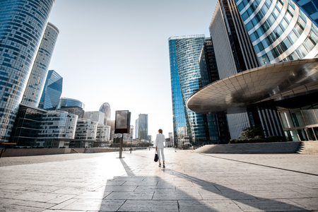 Business woman at the financial district with beautiful skyscrapers on the background during the morning light in Paris. Wide panoramic view Foto de archivo