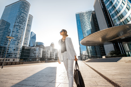 Business woman at the financial district with beautiful skyscrapers on the background during the morning light in Paris