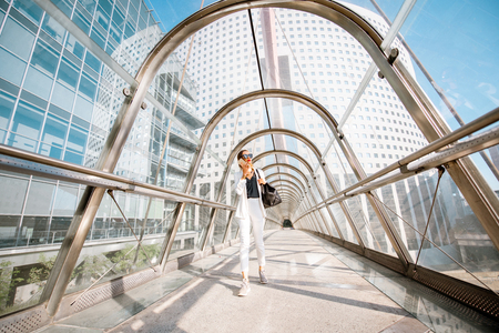 Business woman walking with bag and phone on the modern covered bridge at the business center in Paris 스톡 콘텐츠