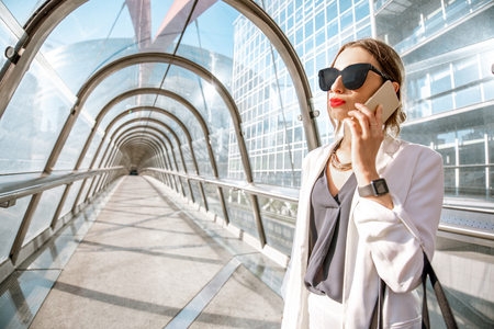 Portrait of a business woman talking with phone on the modern covered bridge at the business center in Paris
