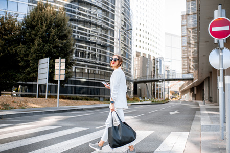 Stylish business woman crossing the street at the financial district with modern buildings on the background in Paris Banco de Imagens