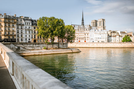 View on the riverside with beautiful buildings and Notre-Dame cathedral in Paris, France