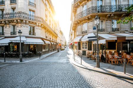 Widok na ulicę z pięknymi budynkami i tarasem kawiarni podczas porannego światła w Paryżu