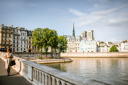 Woman walking on the bridge with beautiful view on the riverside with Notre-Dame cathedral in Paris, France Фото со стока