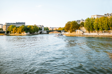 Landscape view on the riverside from the boat sailing on Seine river during the sunset in Paris