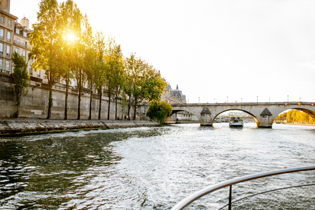 View on the riverside from the boat sailing on Seine river during the sunset in Paris Banco de Imagens