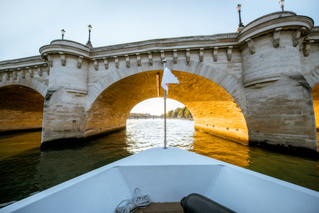 View on the bridge from the boat sailing on Seine river during the sunset in Paris