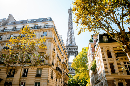Beautiful street view with old residential buildings and Eiffel tower during the daylight in Paris Фото со стока