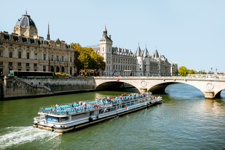 Landscape view of Seine river with Justice palace and tourist boat in Paris