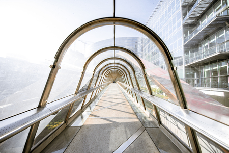 Modern covered pedestrian bridge in form of arch in La Defense financial district in Paris