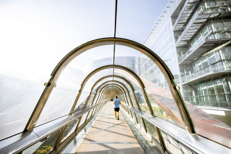Modern covered pedestrian bridge in form of arch with man running in La Defense financial district in Paris