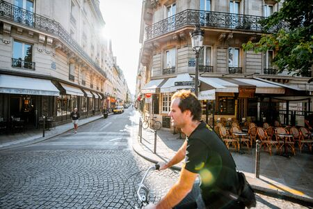PARIS, FRANCE - August 31, 2018: Street view with french cafe and man rides a bicycle during the moorning light in Paris 에디토리얼