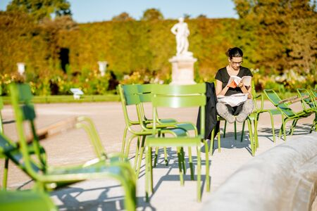 PARIS, FRANCE - September 01, 2018: Woman reading book on the famous green chairs in Tuileries park near the fountain in Paris