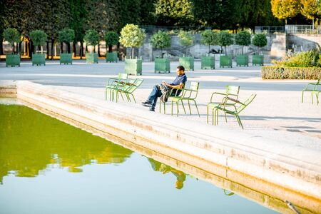 PARIS, FRANCE - September 01, 2018: Man sitting on the famous green chairs in Tuileries park near the fountain in Paris