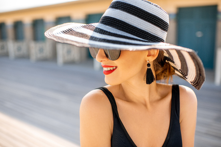 Close-up portrait of a beautiful woman in striped hat on the beach near the old locker rooms in Deauville, famous french resort in Normandy
