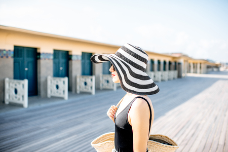 Portrait of a beautiful woman in striped hat on the beach near the old locker rooms in Deauville, famous french resort in Normandy