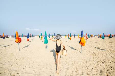 Woman walking on the beach with colorful umbrellas in Deauville, famous french resort in Normandy Banque d'images - 110472843
