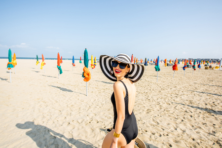 Woman walking on the beach with colorful umbrellas in Deauville, famous french resort in Normandy