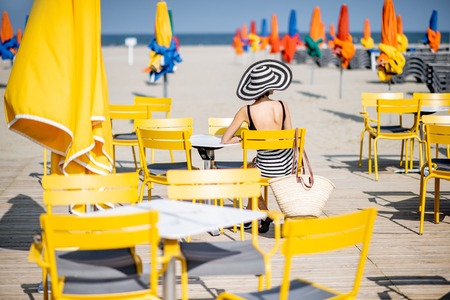 Woman sitting on the yellow chairs on the beach with colorful umbrellas in Deauville, France Banque d'images - 110473552