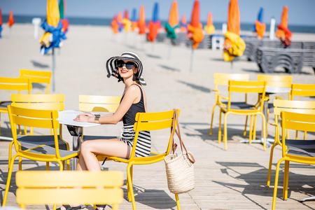Woman sitting on the yellow chairs on the beach with colorful umbrellas in Deauville, France Banque d'images - 110473564