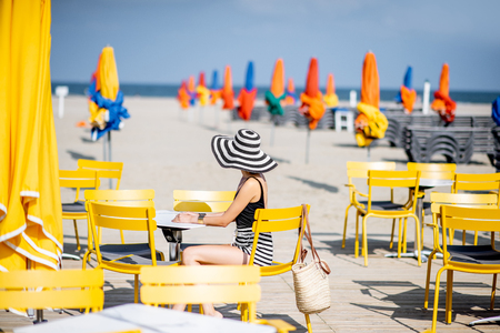 Woman sitting on the yellow chairs on the beach with colorful umbrellas in Deauville, France Banque d'images - 110476348