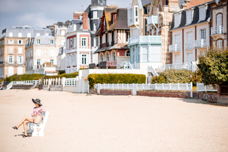 Woman sitting on the bench enjoying beautiful view on the beach in Trouville city, famous french resort in Normandy