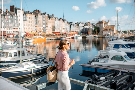 Young woman tourist enjoying beautiful view on the harbour traveling in Honfleur town in Normandy, France Archivio Fotografico